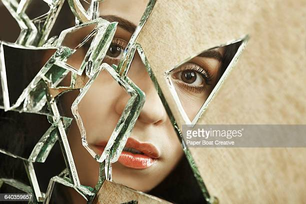Close up of a woman looking through broken glass