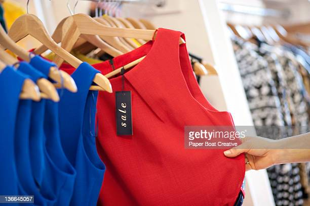close up of a woman selecting a red dress on sale - cocktail dress stock pictures, royalty-free photos & images