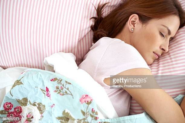 close up of a woman sleeping in bed