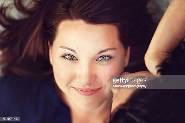 close up of a woman smiling while receiving a kiss - lesbica bacio foto e immagini stock