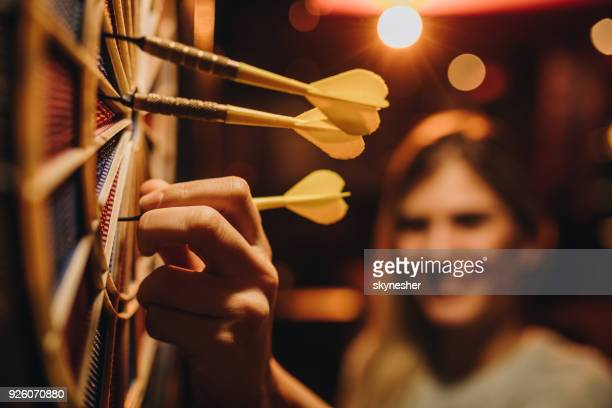 Close up of a woman taking darts out of dart board.