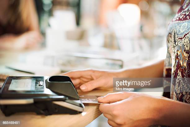 Close up of a woman using a credit card reader in a shop.