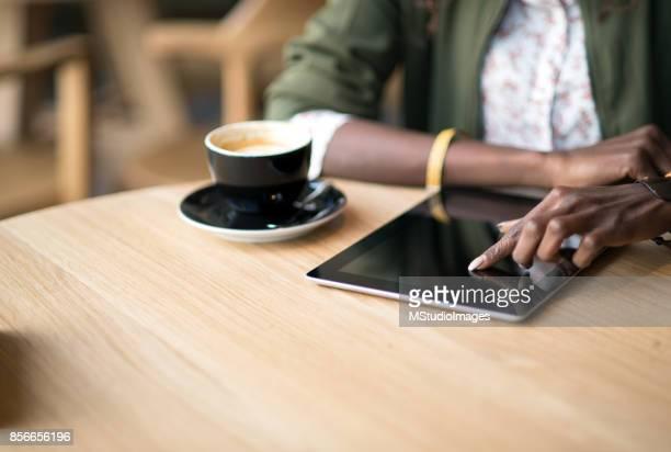 nahaufnahme einer frau mit digital-tablette - couchtisch stock-fotos und bilder