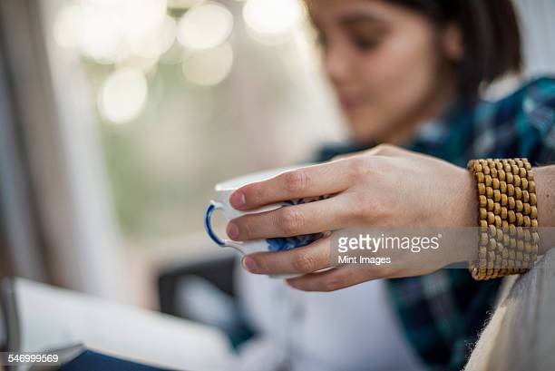 Close up of a womans hand holding a tea cup, wearing a bracelet.