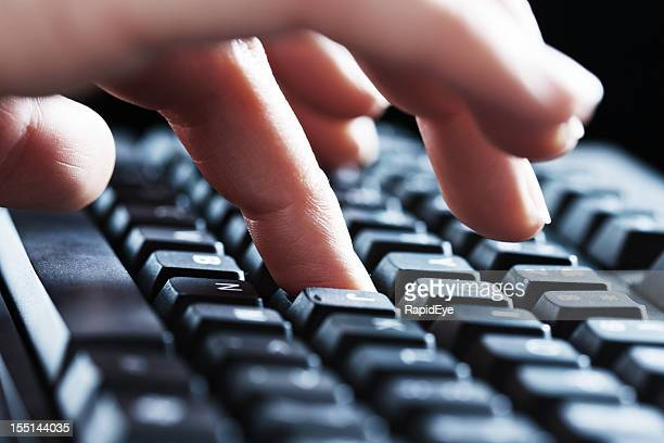 Close up of a woman's hands typing on black keyboard