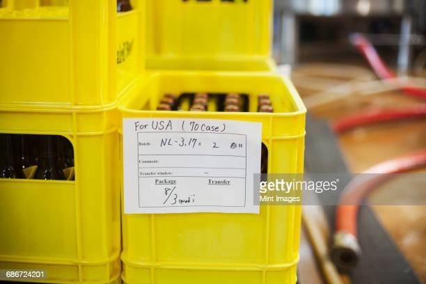 Close up of a yellow plastic crate with beer bottles, a handwritten label.