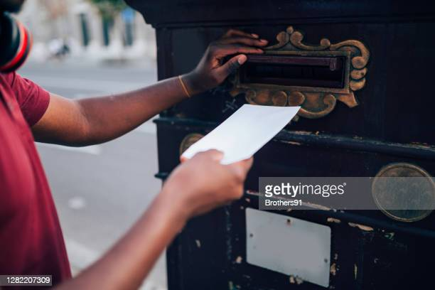 close up of a young african american voting by mail - polling station stock pictures, royalty-free photos & images