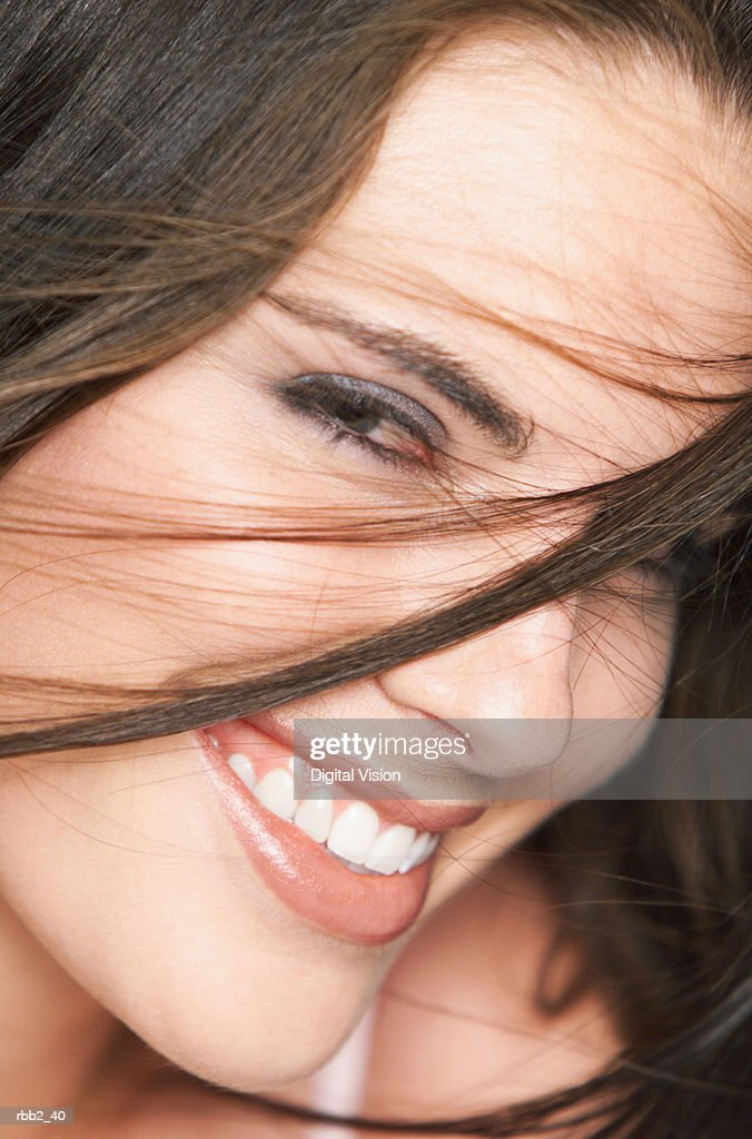 close up of a young attractive caucasian brunette who smile into the camera as her hair is tossed in front of her face : Foto de stock