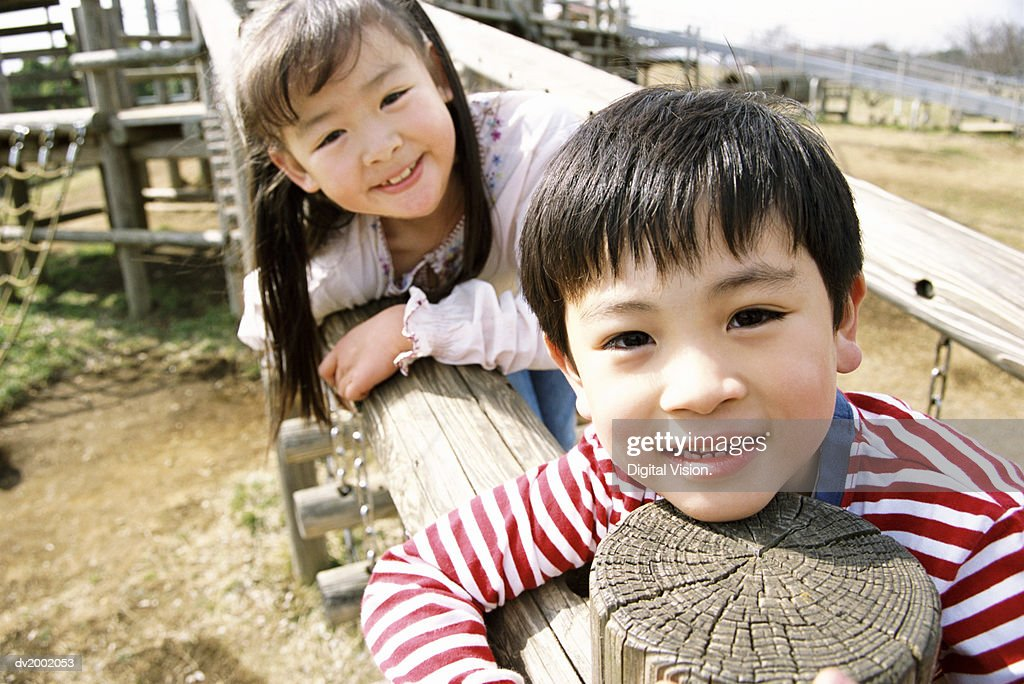 Close Up of a Young Boy and Girl Playing on an Adventure Playground : Stock Photo