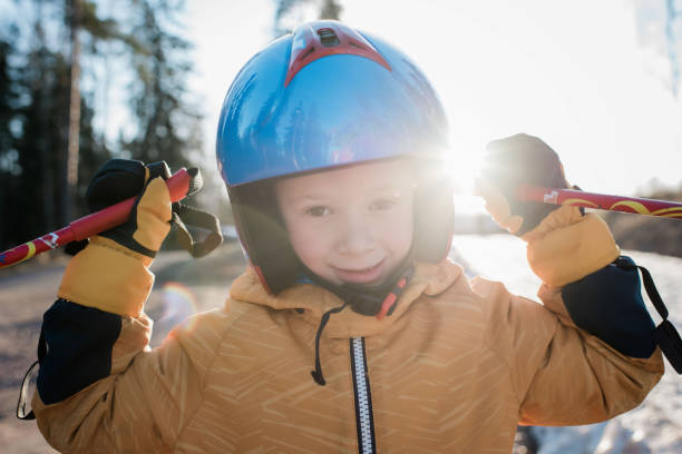 close up of a young boy wearing a ski helmet holding poles at sunset