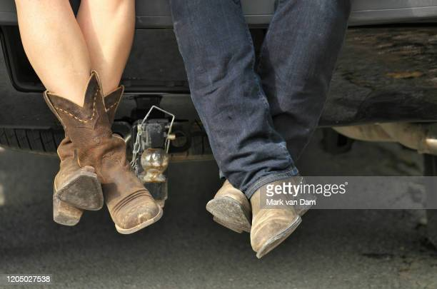 close up of a young couple's cowboy boots as they sit hip to hip in the tailgate of a pickup truck - country and western stock pictures, royalty-free photos & images