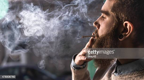 close up of a young hipster smoking cigarette. - weed stock photos and pictures