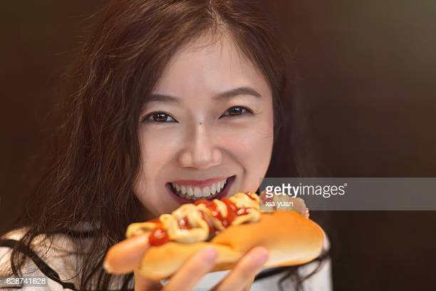 Close up of a young woman eating a hot dog