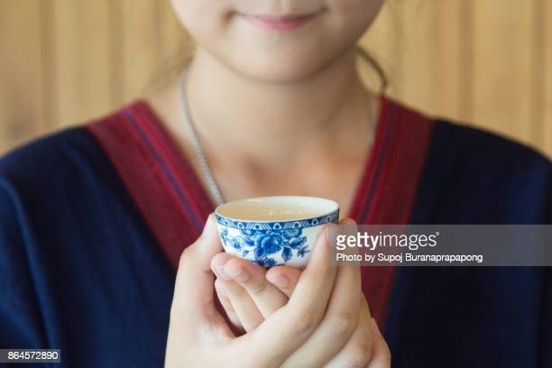 Close up of a young woman hands holding a hot chinese tea cup in traditional cloth