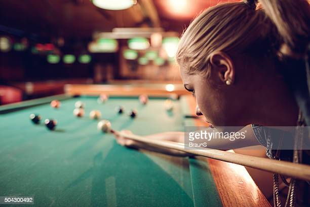 Close up of a young woman playing snooker.