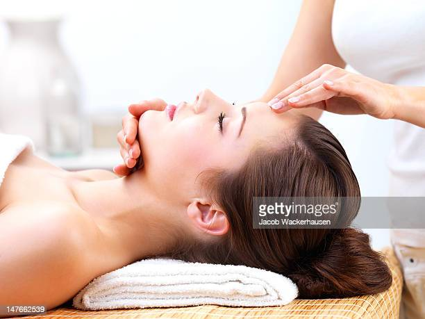 close up of a young woman receiving facial massage - sensual massage stock photos and pictures