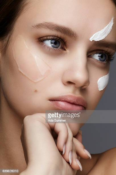 close up of a young woman with cream and gel on her face