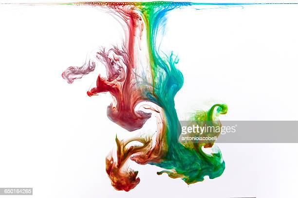 Close up of acrylic paints mixing in water