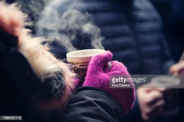close up of adult holding a mug of hot glühwein at a german christmas market - weihnachtsmarkt stock-fotos und bilder