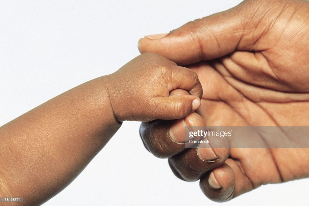 Close up of adult holding baby's hand : Stockfoto