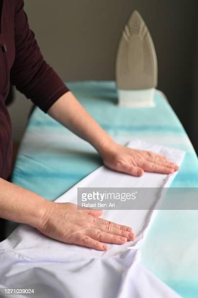 close up of adult woman hands during ironing clothes - rafael ben ari stock-fotos und bilder