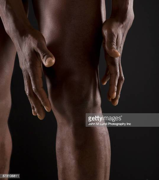 Close up of African American athlete reaching for knee