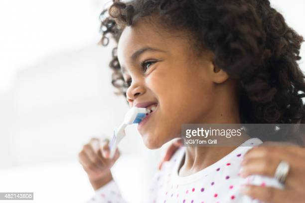 Close up of African American girl brushing teeth