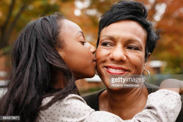 Close up of African American girl kissing mother