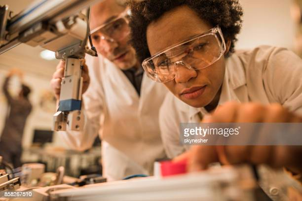 Close up of African American scientist testing a machine in laboratory.
