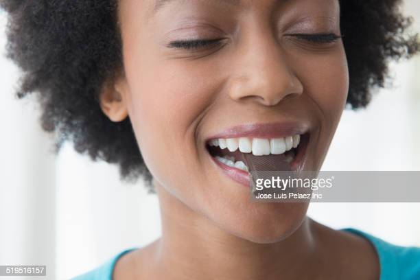 close up of african american woman eating square of chocolate - 噛む ストックフォトと画像