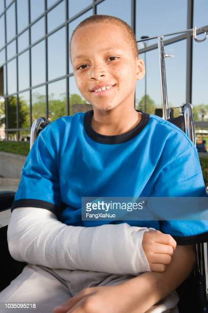 close up of african boy with broken arm in wheelchair outdoors - broken arm stock pictures, royalty-free photos & images