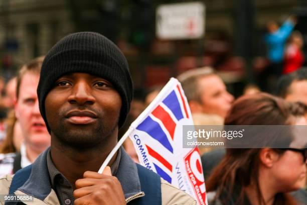 Close up of African ethnicity man holding British union jack flag at Royal Wedding, London, UK