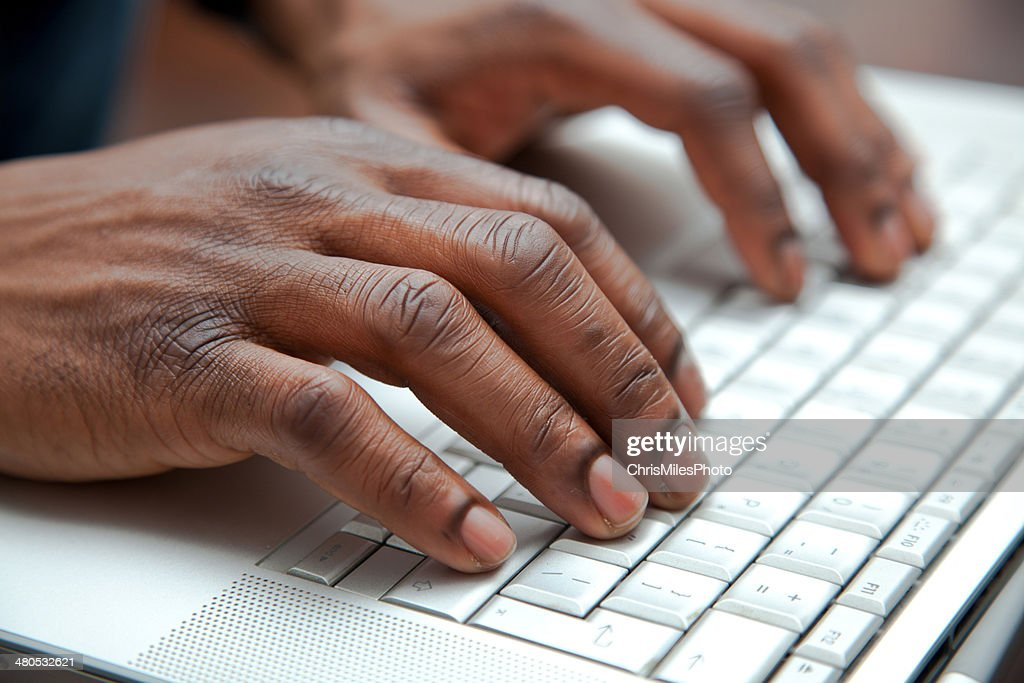 Close up of African hands on a keyboard : Stockfoto