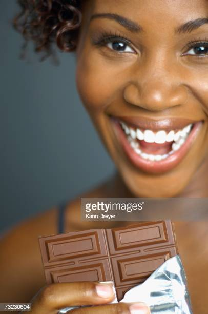 Close up of African woman eating chocolate