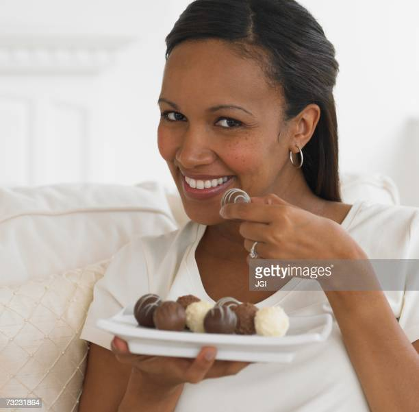 Close up of African woman eating chocolate truffles