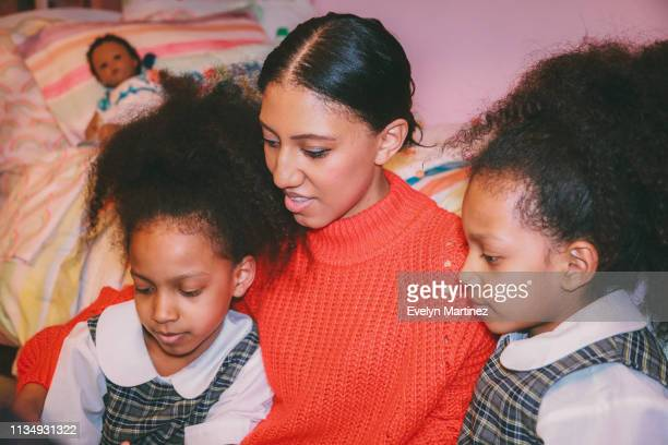 Close up of Afrolatina mom and twin daughters looking away from camera. Mother is wearing an orange colored sweater. Twins are wearing plaid school uniform. Out of focus in the background is a bed and a baby doll.