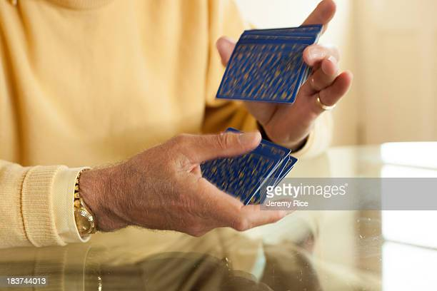 close up of aged hands shuffling playing cards - shuffling stock photos and pictures
