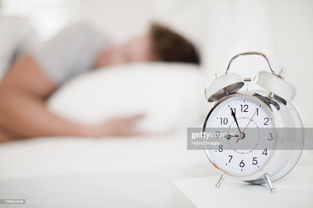Close Up Of Alarm Clock On Bedside Table : Stock Photo