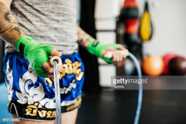 close up of amateur kickboxers using skipping rope - muay thai imagens e fotografias de stock