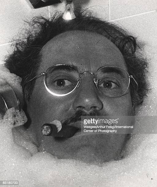 Close up of American comic actor and performer Groucho Marx in a bath tub with lots of soapy bubbles fully clothed smoking a cigar New York 1952...