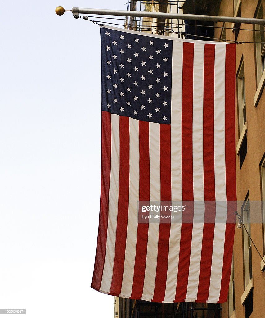 Close up of American flag hanging from building : Stock Photo