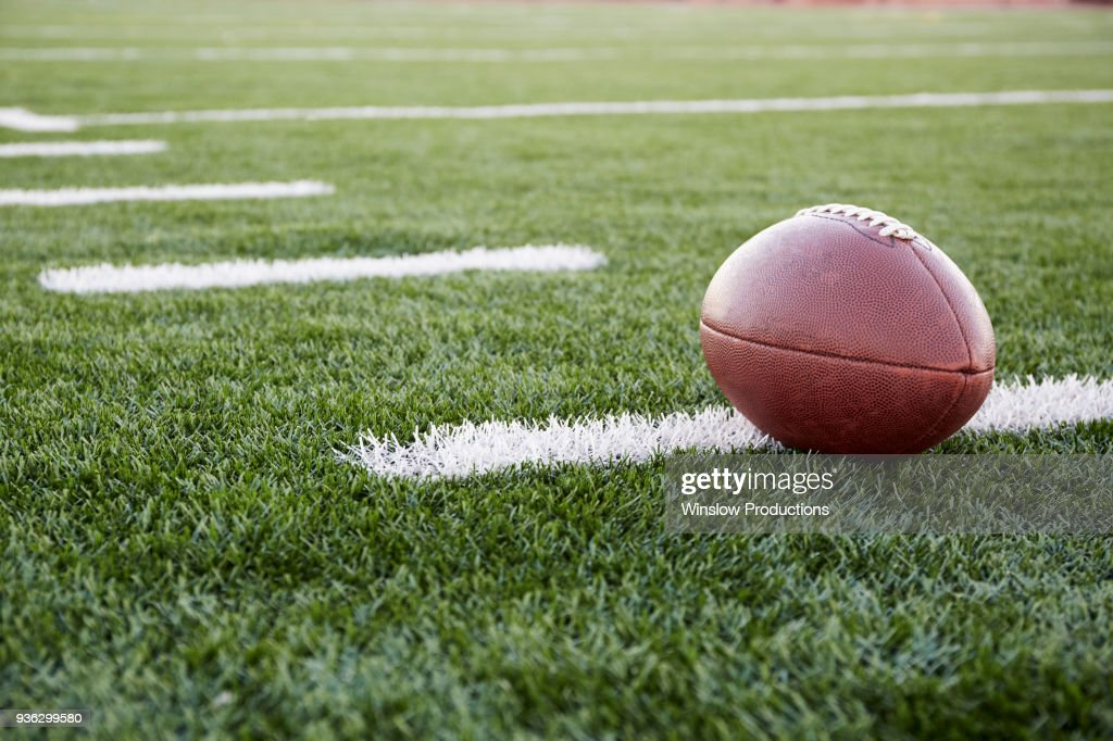 Close up of American football ball on green playing field : Stock Photo