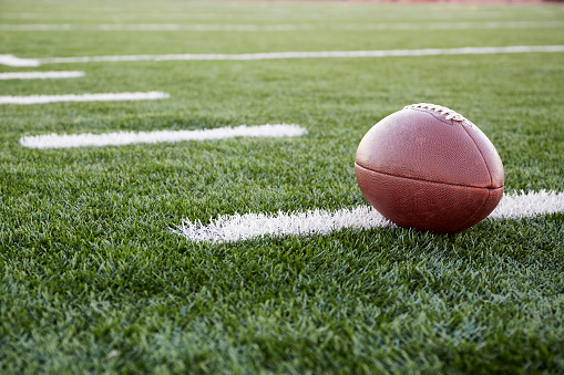 Close up of American football ball on green playing field - gettyimageskorea