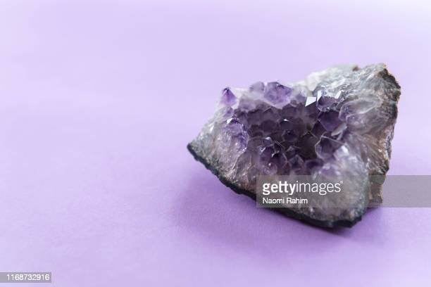 close up of amethyst crystal geode on a puple background - amethyst stock pictures, royalty-free photos & images