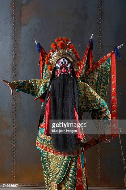 Close up of an actor dressed as a traditional Beijing Opera Army General posing in front of an industrial rusting steel wall with flags and a sword.