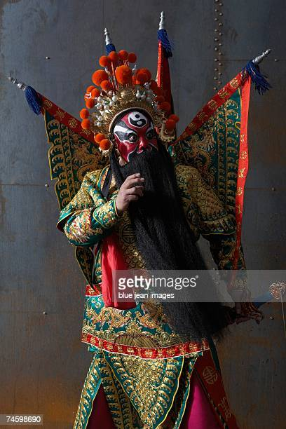 Close up of an actor dressed as traditional Beijing Opera Army General posing in martial arts stance.