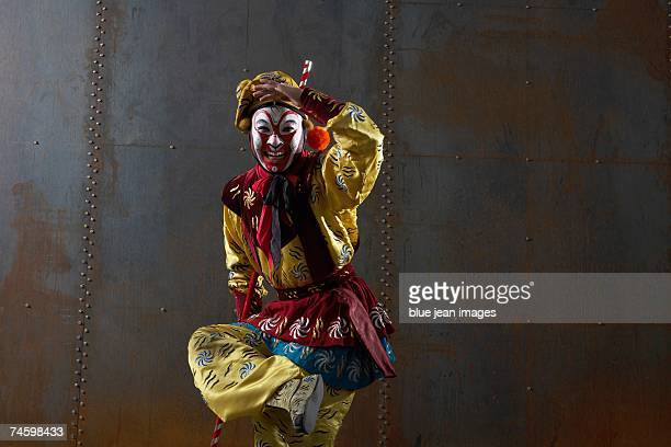 close up of an actor dressed as traditional beijing opera comedian posing on one leg with a staff in front of an industrial rusting steel wall. - beijing opera stock photos and pictures