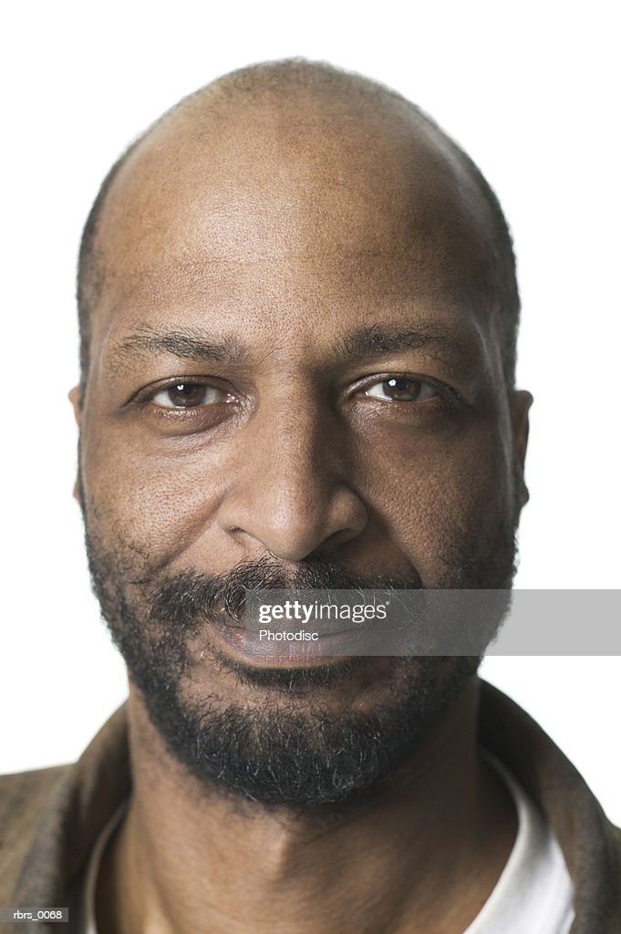 close up of an adult bald man with a beard as he looks seriously into the camera : Foto de stock