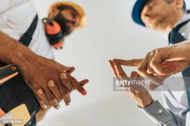 close up van een architect zijn werknemer dingen te doen uit te leggen. - herbouwen stockfoto's en -beelden