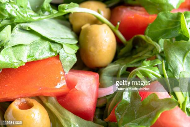 Close up of an arugula salad The vegetarian food is mixed with pieces of tomatoes and olives Healthy food green salad